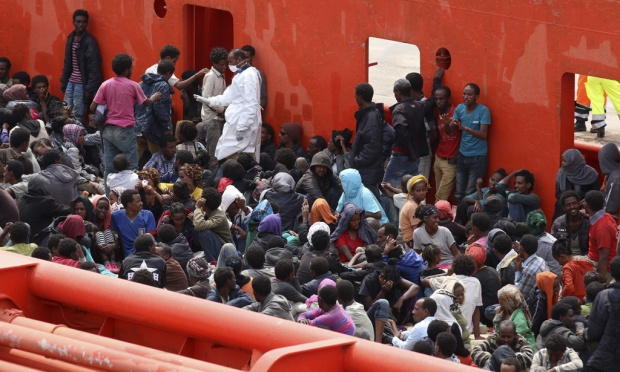 Migrants are seen aboard a navy ship before being disembarked in the Sicilian harbour of Augusta