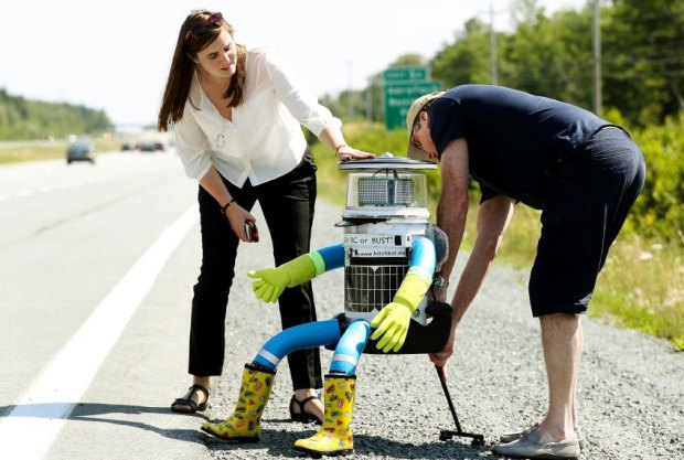 Dr. Frauke Zeller and Dr. David Smith place their anthropomorphic robot named hitchBOT onto the shoulder of Highway 102 outside of Halifax, Nova Scotia